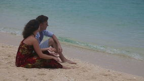 Happy couple on tropical beach. Happy young couple sitting on a tropical beach.Man throws stone into the sea.Stone jumps on the waves.Love and the romantic on stock video