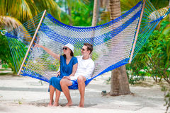 Happy couple on tropical vacation relaxing in hammock royalty free stock images