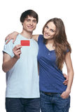 Happy couple. In tshirts hugging, men showing blank credit card, on white background Royalty Free Stock Image