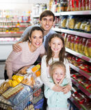 Happy couple with two daughters shopping Royalty Free Stock Images