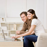 Happy couple typing on laptop Stock Photography
