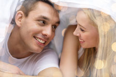 Happy couple under blanket in bed Royalty Free Stock Photography