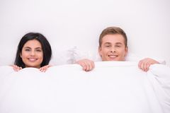 Happy couple is under blanket looking at camera Royalty Free Stock Photos