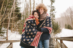 Happy couple under stars and stripes rug in winter park Royalty Free Stock Image
