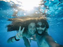 Happy couple under the water in a pool royalty free stock image