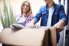 Happy Couple Unloading Moving Van. Portrait of smiling men and women putting cardboard box into moving van stock photography