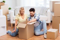Happy couple unpacking boxes at new home royalty free stock images