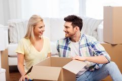 Happy couple unpacking boxes at new home stock photos