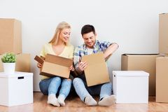 Happy couple unpacking boxes at new home. Mortgage, moving and real estate concept - happy couple unpacking boxes at new home royalty free stock photo