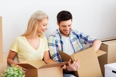 Happy couple unpacking boxes at new home. Mortgage, moving and real estate concept - happy couple unpacking boxes at new home royalty free stock photos