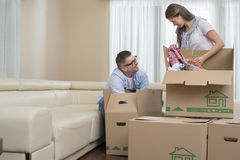 Happy couple unpacking cardboard boxes in new home Royalty Free Stock Image