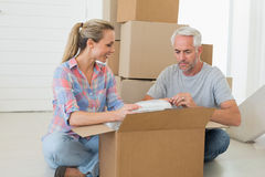 Happy couple unpacking cardboard moving boxes Royalty Free Stock Image