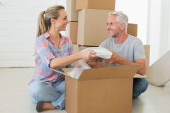 Happy couple unpacking cardboard moving boxes Royalty Free Stock Images