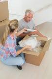 Happy couple unpacking cardboard moving boxes Stock Image