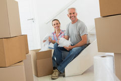 Happy couple unpacking cardboard moving boxes Stock Photos