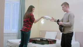 Happy couple unpacking suitcase just coming to a hotel room. Professional shot in 4K resolution. 068. You can use it e.g. in your commercial video, business stock video footage