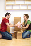 Happy couple unpacking in their new home Royalty Free Stock Photos
