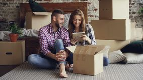 Happy couple is unpacking things after relocation opening box and looking at photos talking and laughing together