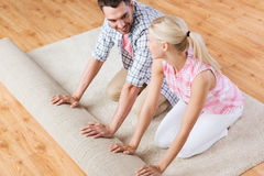 Happy couple unrolling carpet or rug at home Royalty Free Stock Photo