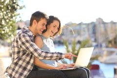 Happy couple uses a laptop on vacation. Happy couple uses a laptop sitting in a port on summer vacation Royalty Free Stock Image