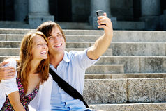 Happy couple uses a smartphone to take a picture Stock Images
