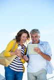 Happy couple using digital tablet against sky Stock Images