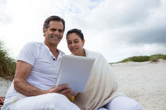 Happy couple using digital tablet on beach Royalty Free Stock Photography