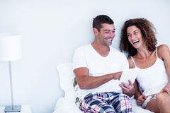 Happy couple using digital tablet on bed Stock Photos
