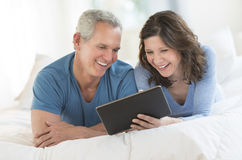 Happy Couple Using Digital Tablet In Bed Stock Photo