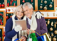 Happy Couple Using Digital Tablet At Christmas Royalty Free Stock Images