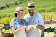 Happy couple using digital tablet at farm Stock Photo
