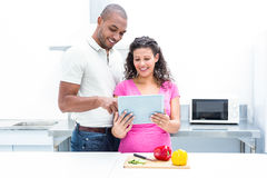 Happy couple using digital tablet in kitchen Stock Image