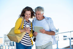 Happy couple using digital tablet and mobile phone Stock Photos