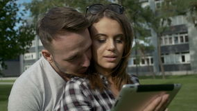Happy couple using digital tablet in park. Young couple sitting on grass working on digital tablet pc stock video