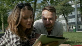 Happy couple using digital tablet in park. Young couple sitting on grass working on digital tablet pc stock footage