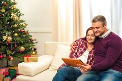 Couple with digital tablet at christmastime. Happy couple using digital tablet while sitting together on sofa at christmastime royalty free stock photography