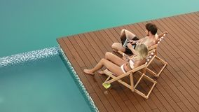 Happy couple using digital technology on relax. Man and woman sunbathing with gadgets near swimming pool. Young people using smartphones on resort stock video footage