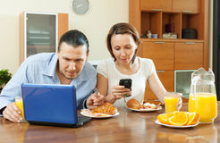 Happy couple using electronic devices during breakfast Royalty Free Stock Images