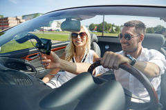 Happy couple using gps navigator in cabriolet car Royalty Free Stock Image