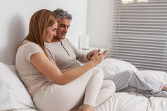 Happy couple using the ipad in the bed Stock Images