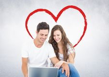 Happy couple using laptop. Against digitally generated red heart Royalty Free Stock Images