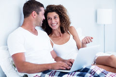 Happy couple using laptop on bed Stock Photo