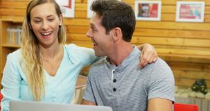 Couple using laptop in cafe 4k. Happy couple using laptop in cafe 4k stock footage
