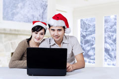 Happy couple using laptop in christmas day Stock Photos
