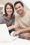 Happy Couple Using Laptop Computer at Home royalty free stock photography