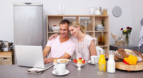 Happy couple using a laptop while having breakfast. In the kitchen Stock Photos