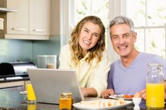 Happy couple using laptop and having breakfast Stock Images