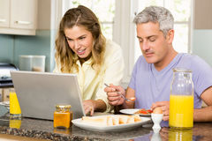 Happy couple using laptop and having breakfast Stock Photo