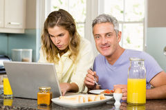 Happy couple using laptop and having breakfast Stock Photography
