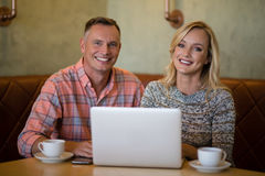 Happy couple using laptop while having coffee Stock Photography